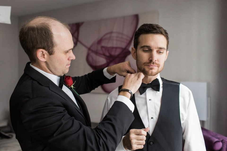 Groom's brother helps him with his bowtie