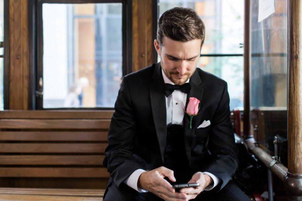 Groom anxiously checks his phone on a trolley