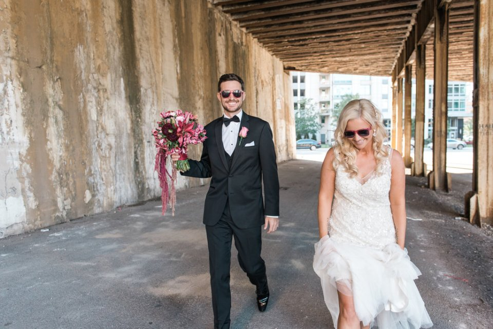 Bride and groom walking through viaduct in Chicago IL