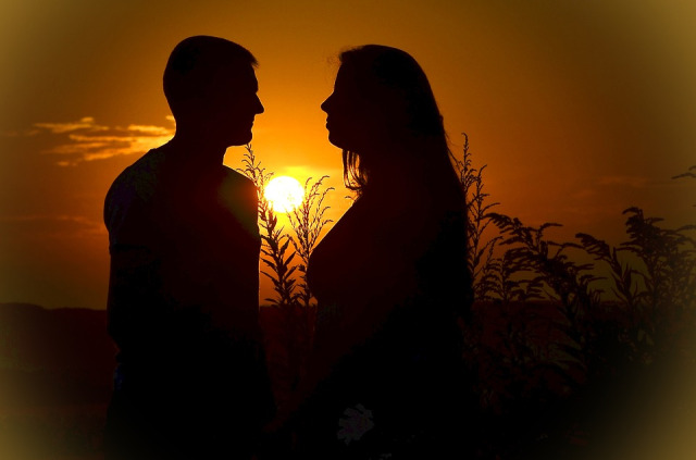 A couple gazing at each other in the sunset.