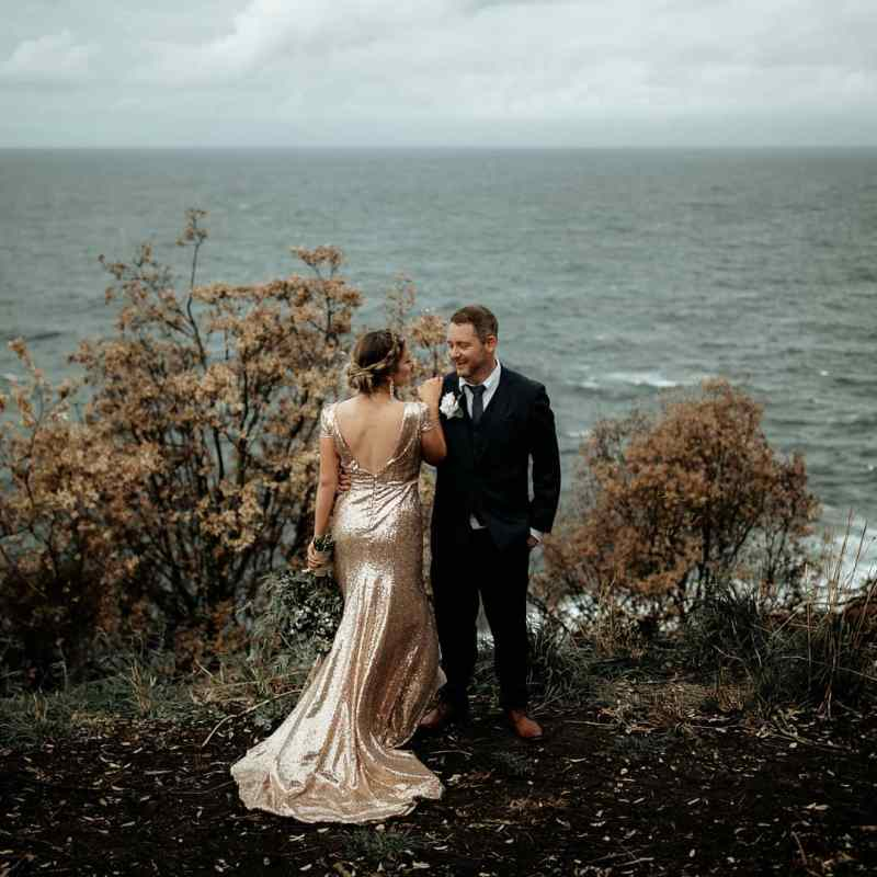 A bride in a wedding dress holds hands with the groom with the sea behind them