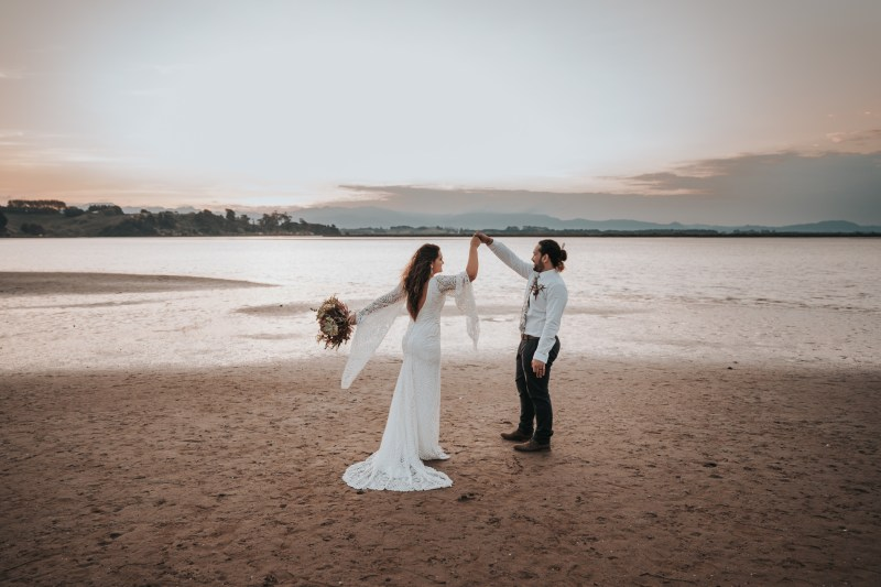A bride and groom celebrate their wedding with a dance on a beach