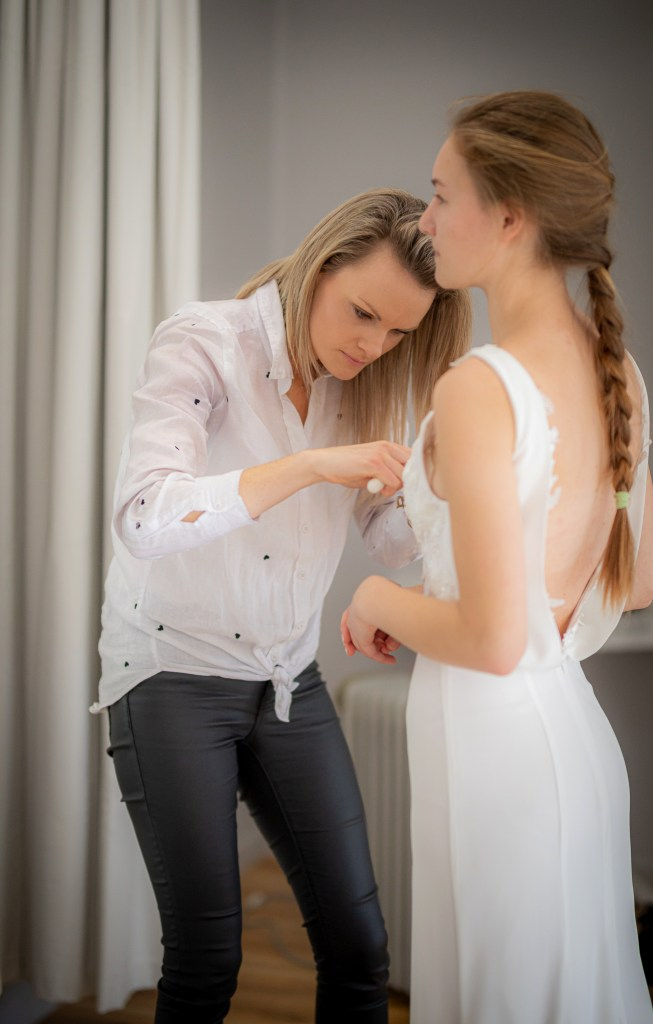 Designer Nicky Hayward adjusts a wedding gown in her Tauranga boutique
