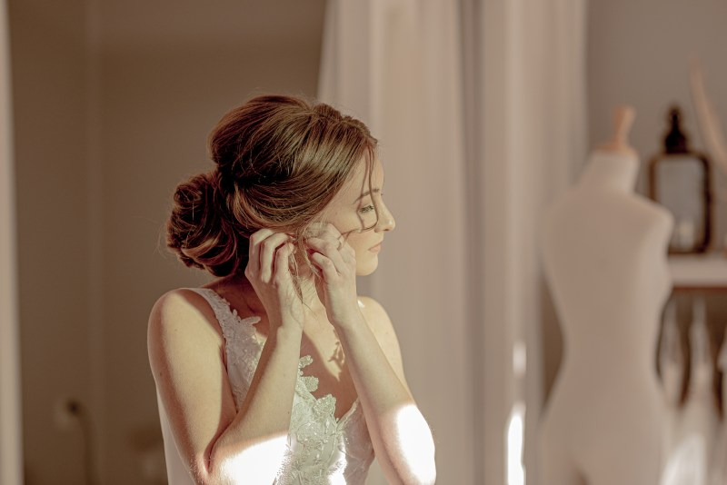 A young woman in a bridal gown adjusts her earrings