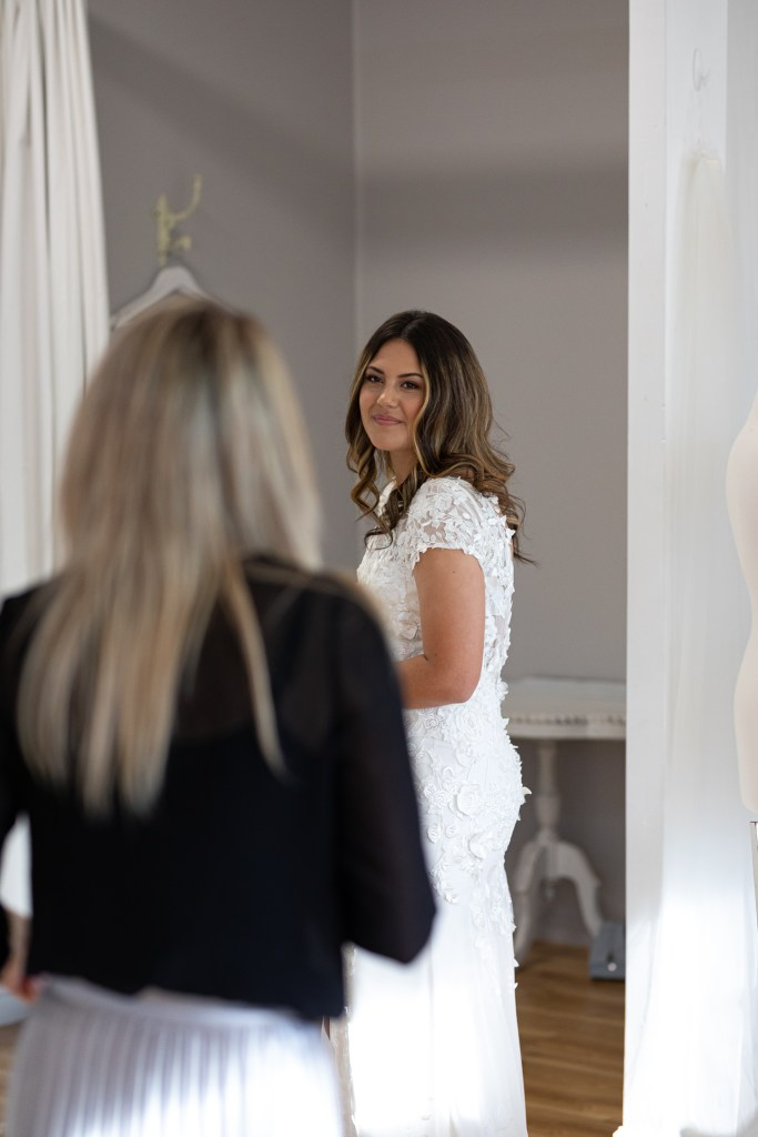 A woman in a wedding gown in a Tauranga boutique looks towards the bridal gown designer