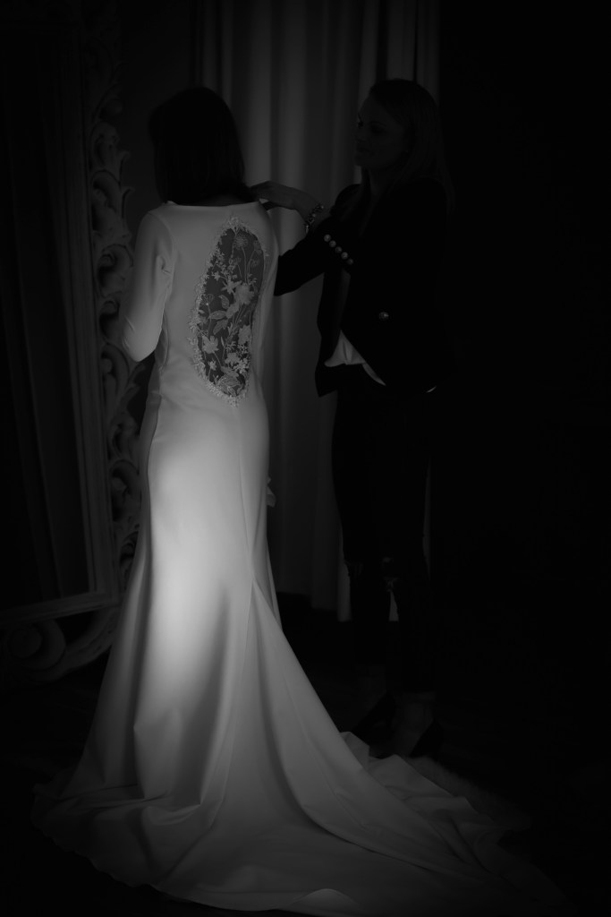 A young woman in a white bridal gown stands in front of a mirror