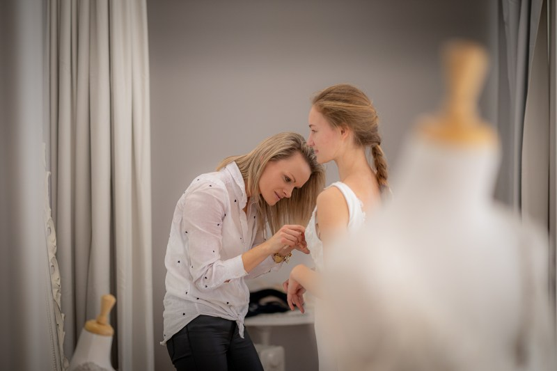 Bridal gown designer Nicky Hayward adjusts a wedding gown in her boutique