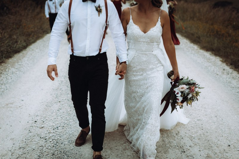 A bride and groom walk hand in hand down the road