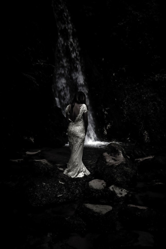 A woman wearing a white wedding dress stands in front of a waterfall near Tauranga
