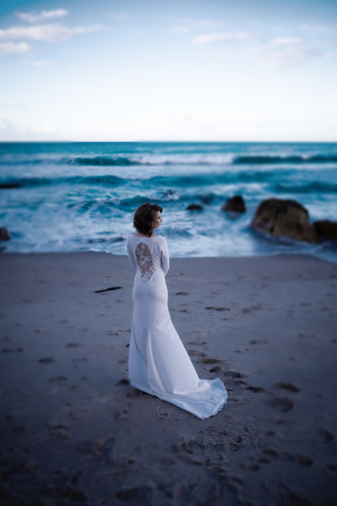 A woman wearing stands on the beach in Mount Maunganui wearing one of the bridal gowns from White Silk Bridal