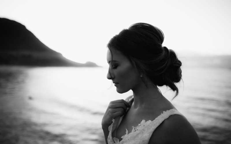A woman looks down in peace as she wears a white bridal gown near Mount Maunganui beach