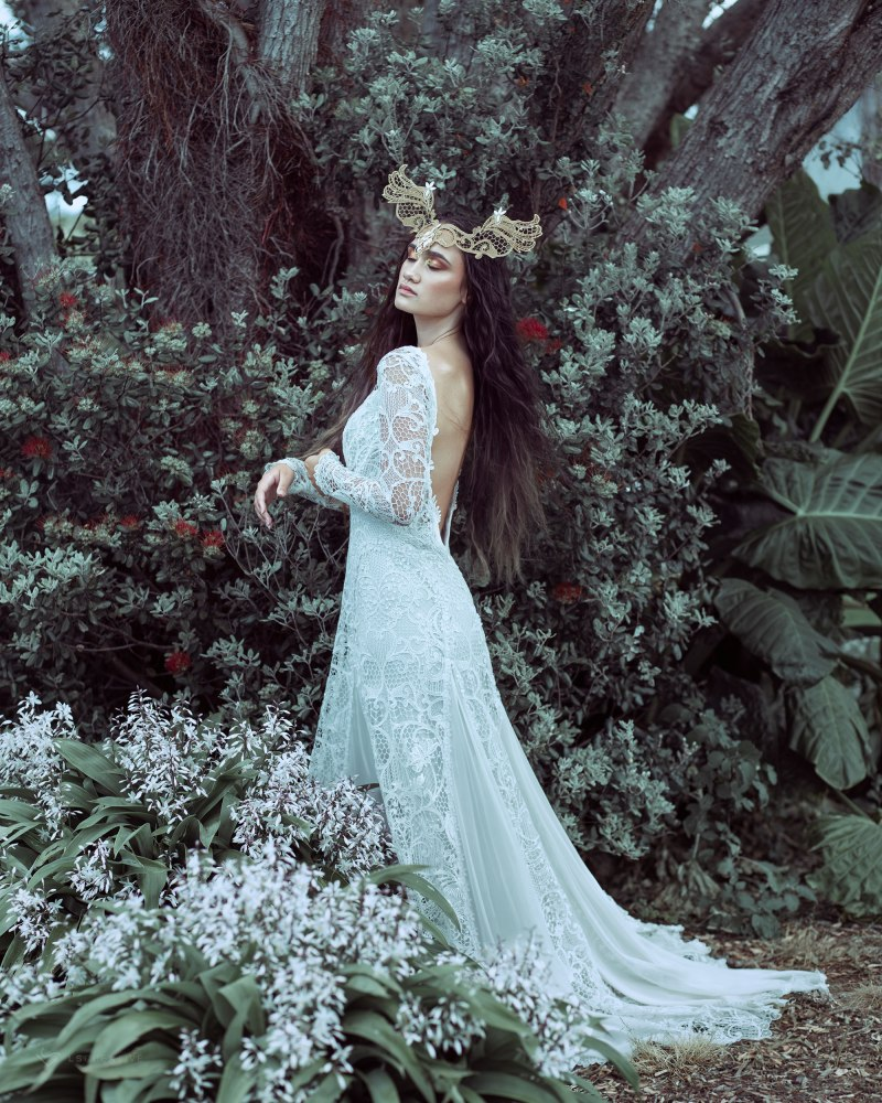 A woman in one of White Silk Bridal's designer bridal gowns stands by a tree