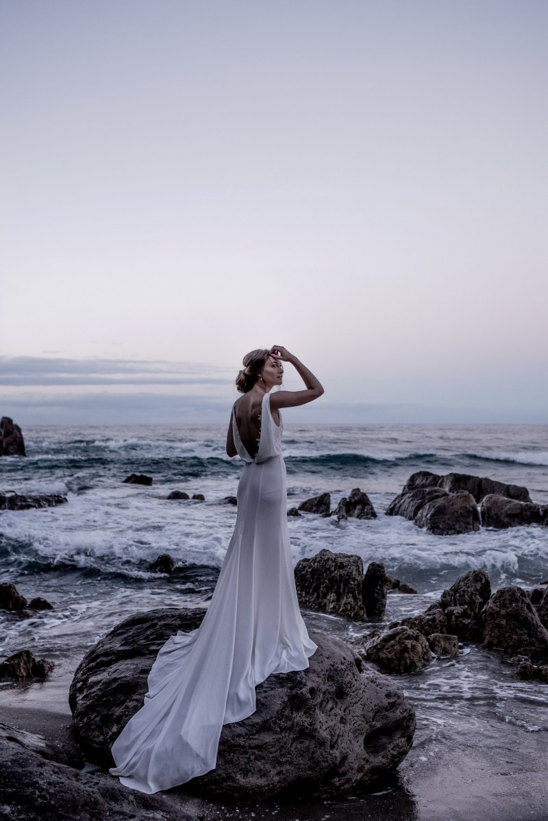 A young woman wearing a white wedding dress stands on a rock on Mount Maunganui Main Beach