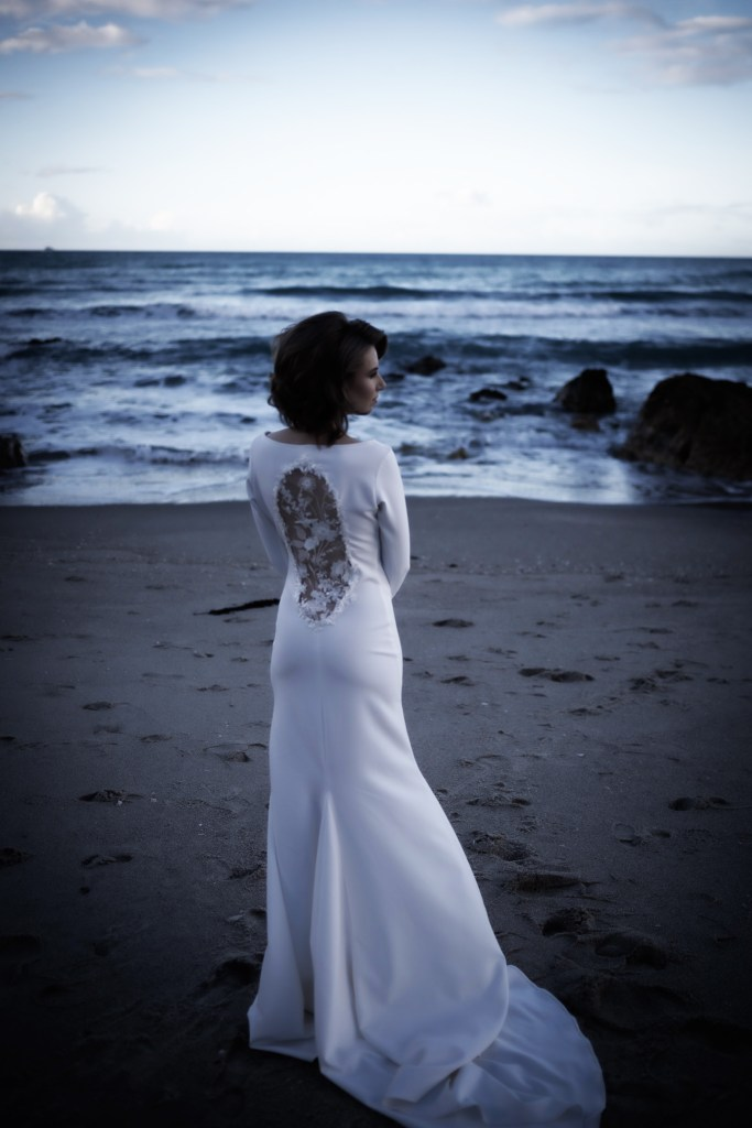 A young woman stands on a beach in Tauranga wearing a bridal gown