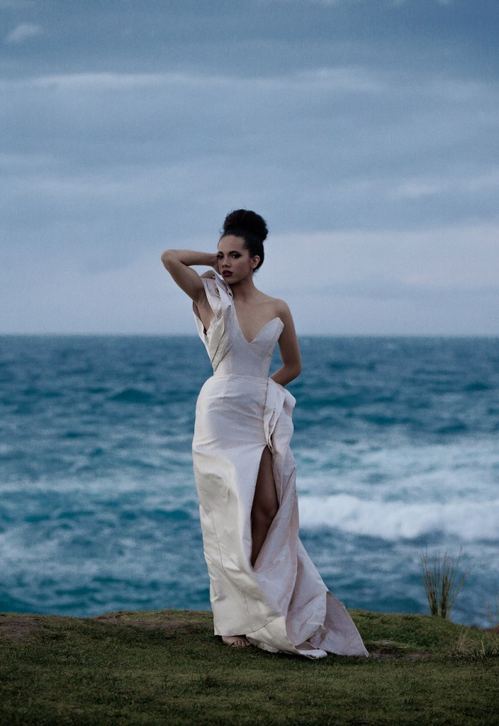 A woman stands by the sea wearing one of White Silk Bridal's designer bridal gowns in Tauranga