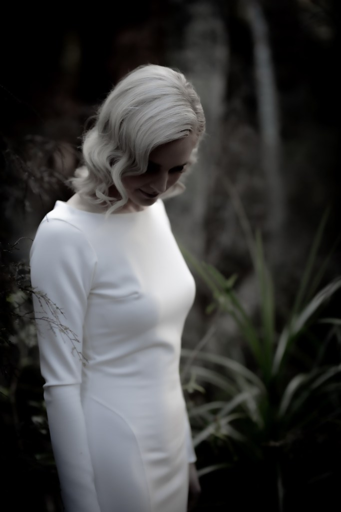 A woman wearing one of a designer bridal gowns collection stands in the bush in Tauranga