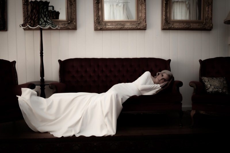 A woman wearing one of the bridal gowns from White Silk Bridal in Tauranga lies on a sofa