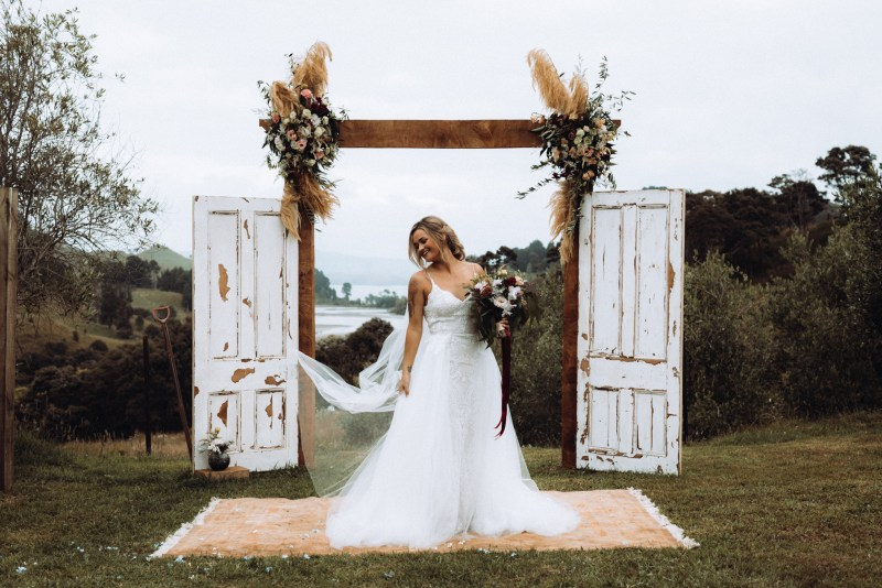 A bride wearing a wedding dress stands outside on her wedding day