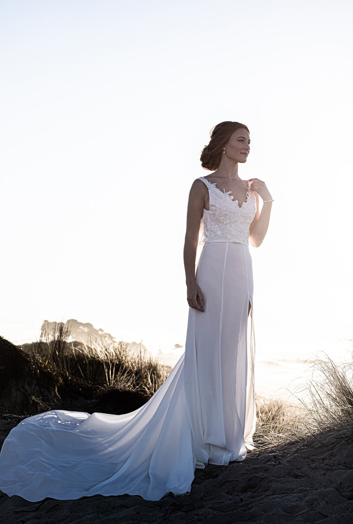 A woman wears a white wedding dress whilst on the beach in Tauranga
