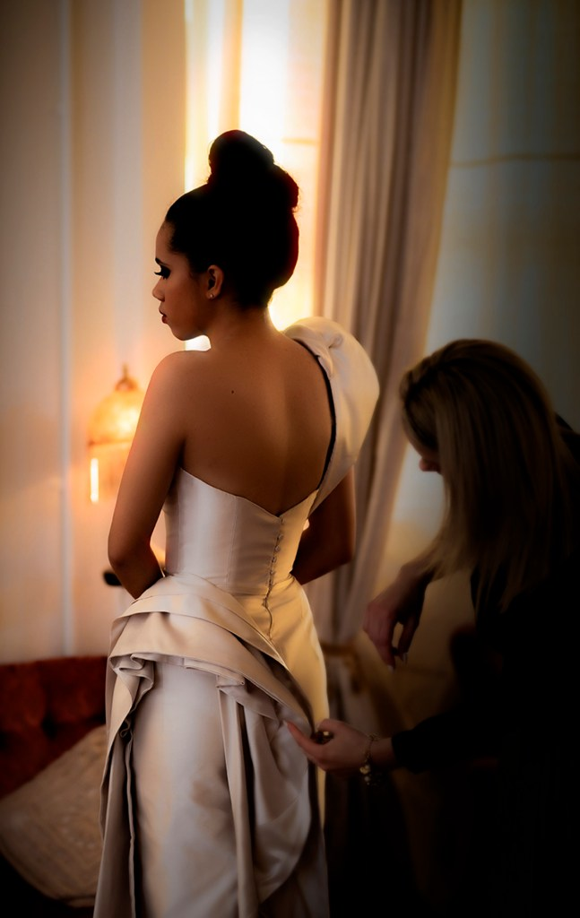 A young woman wears a designer bridal gown in a warmly lit room in Tauranga