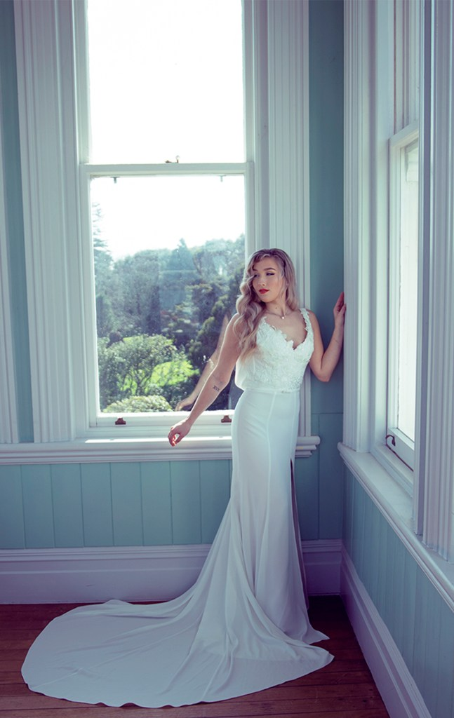 A woman stands by an Auckland window whilst wearing a white bridal gown