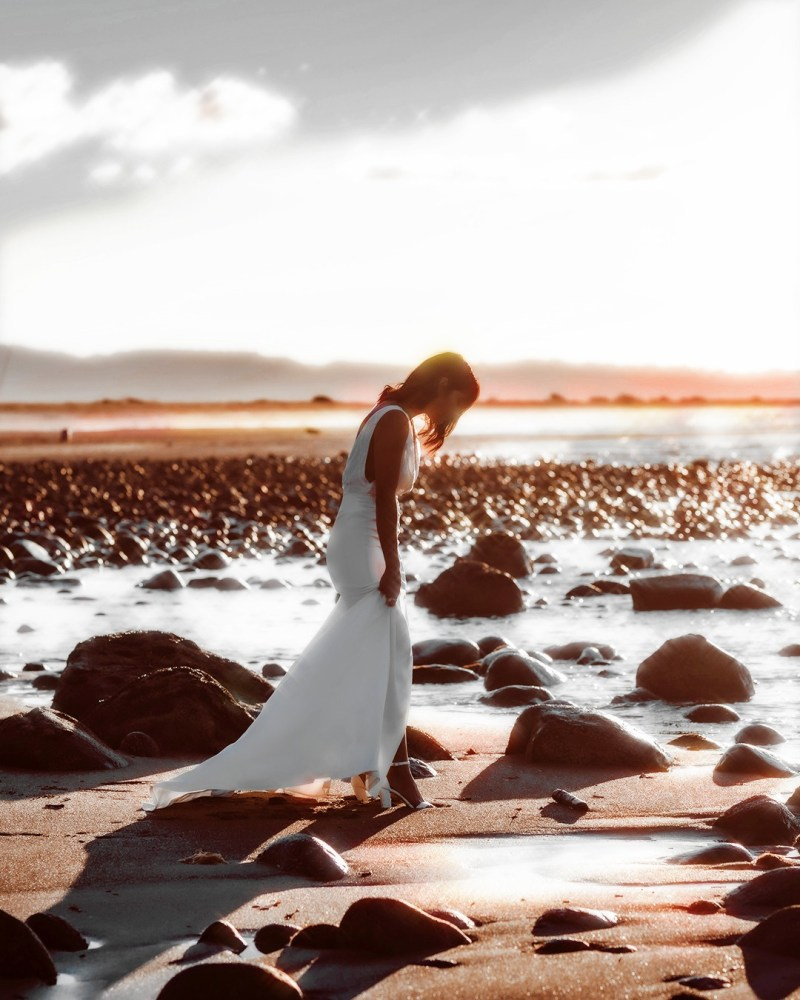 A woman holds her bridal gown at the side as she stands on a beach