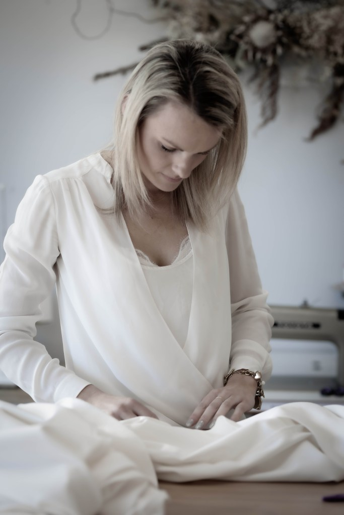 A bridal gown designer makes alterations to a bridal gown in a Tauranga boutique