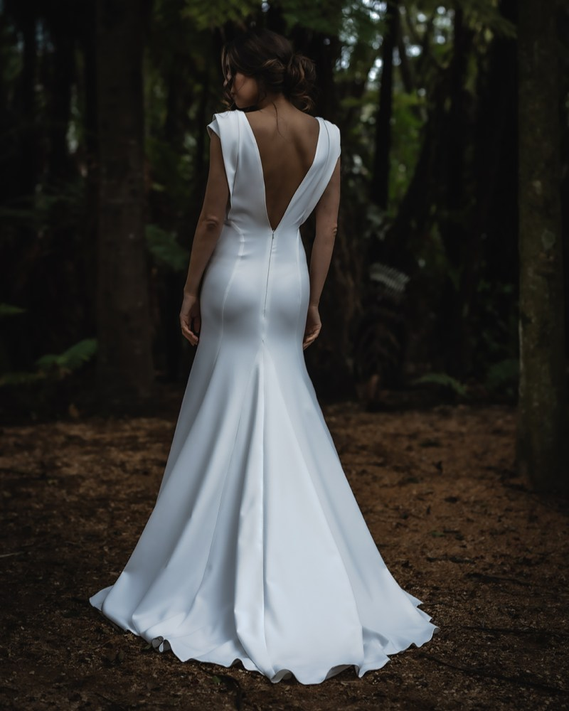 A woman wears a wedding dress in a tree clearing in Tauranga