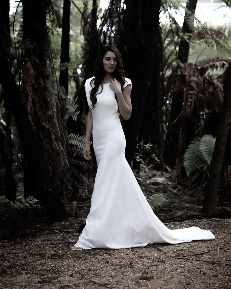 A woman wearing a bridal gown walks through a wood in Tauranga