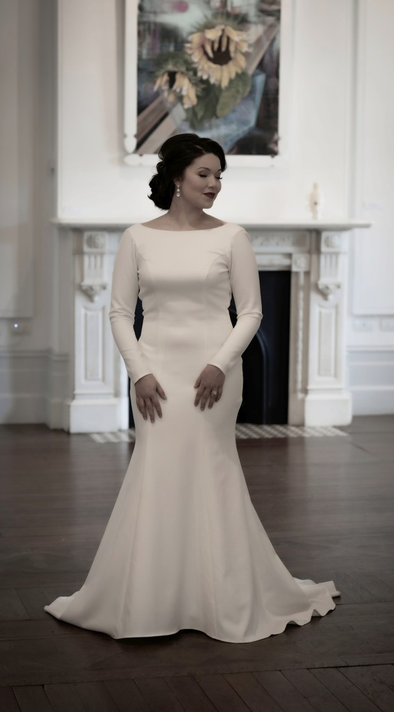 A woman in a white bridal gown stands in a large room