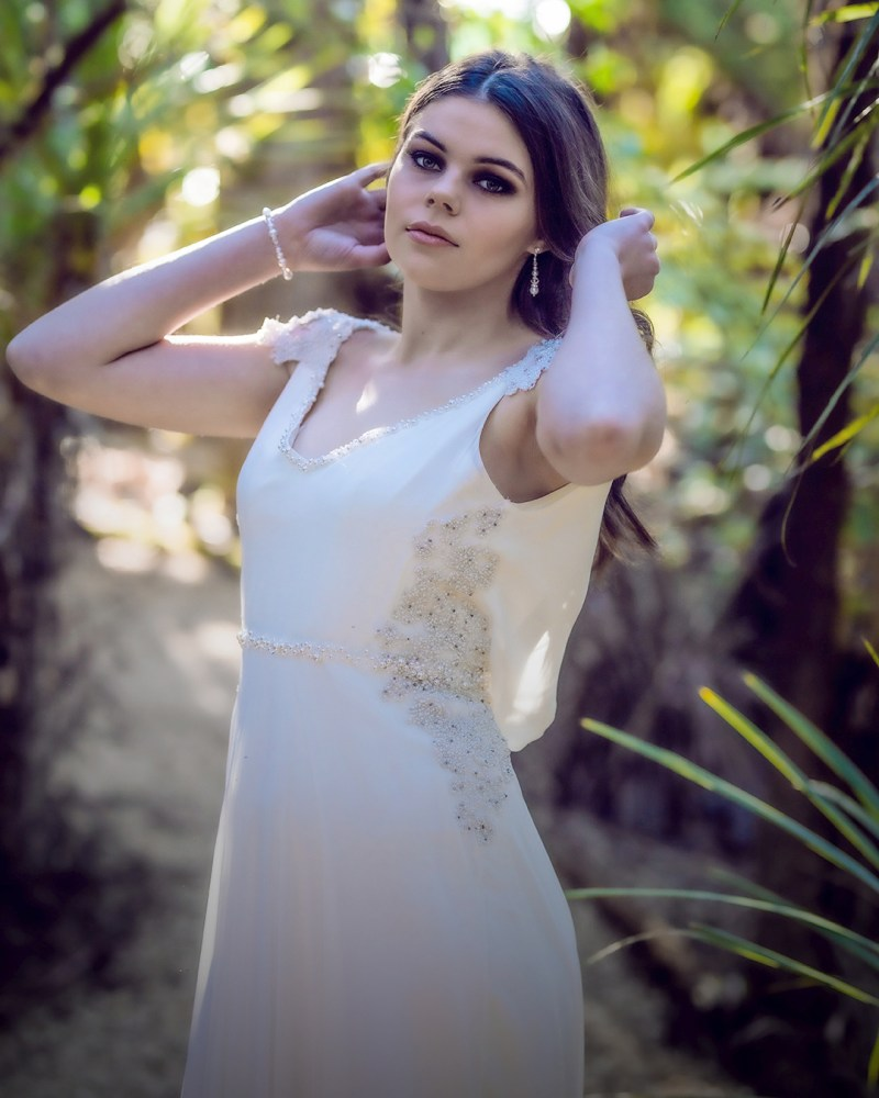 A young woman in a white bridal gown stands in a wood in Tauranga