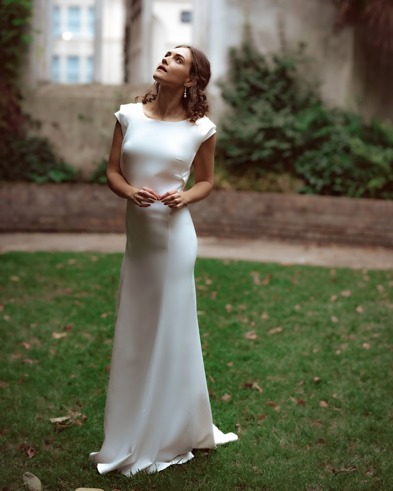 A young woman in a bridal gown stands on grass in a churchyard in London