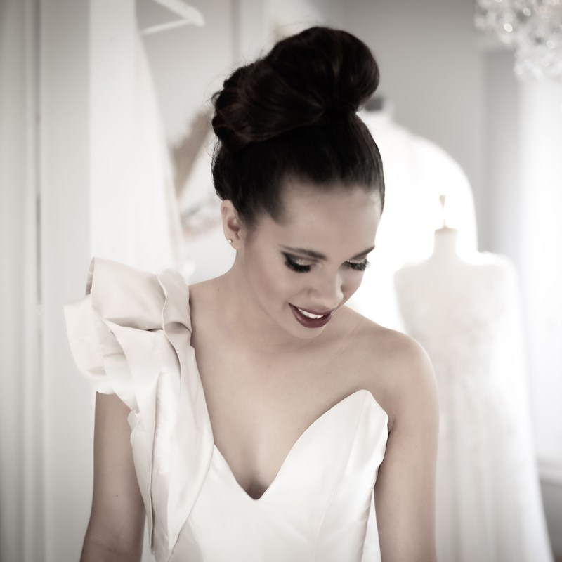 A woman wears a bridal gown whilst standing in the White Silk Bridal boutique
