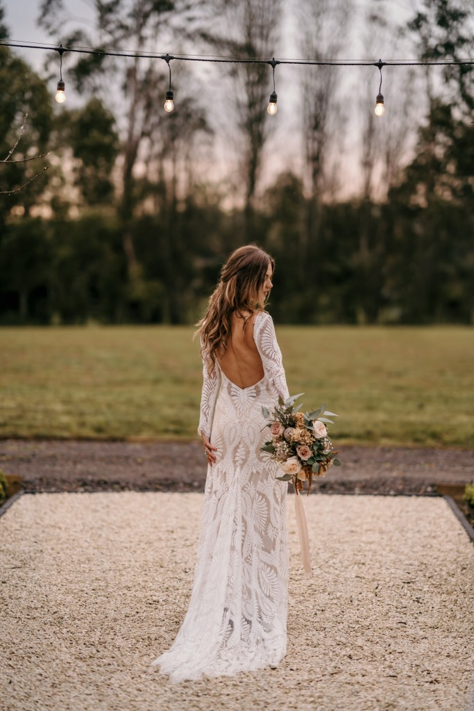 A woman in a white bridal gown stands outside with her back turned