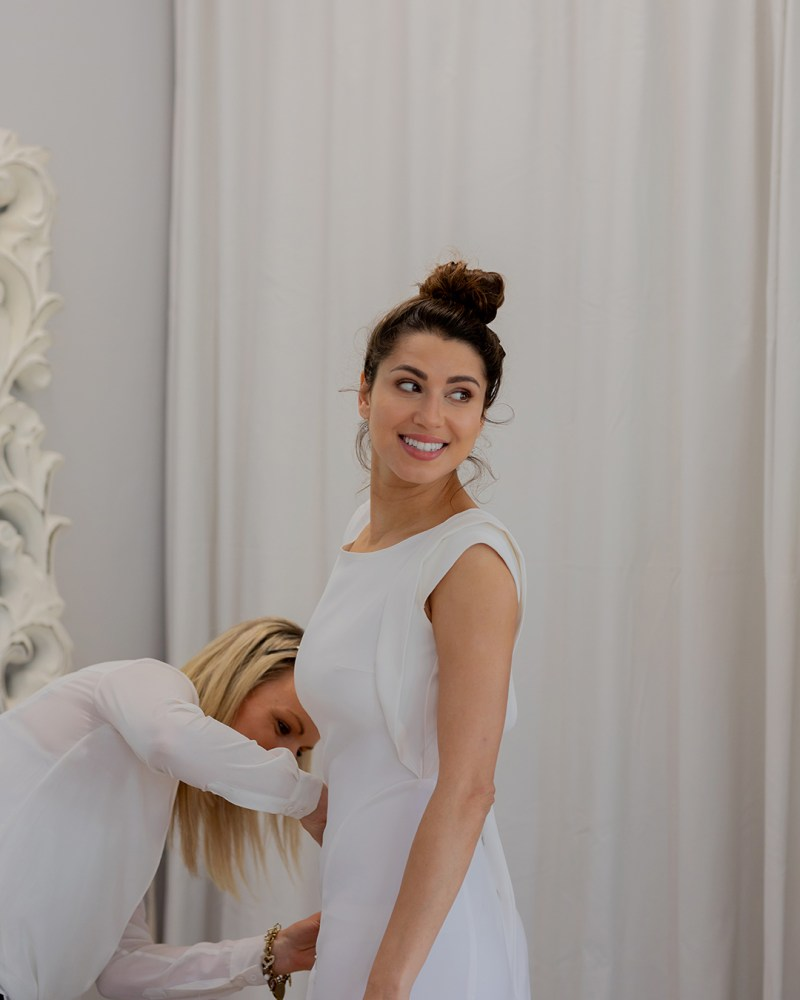 A woman in a bridal gown smiles as she stands in a Tauranga bridal boutique