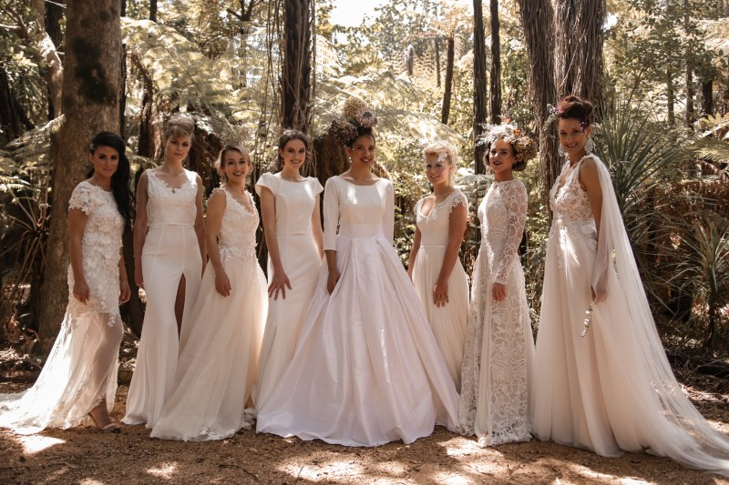 Eight women in different bridal gowns stand side by side by trees