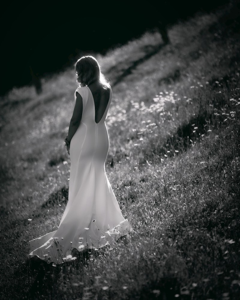A woman in a white bridal gown stands in a field with her back to the camera