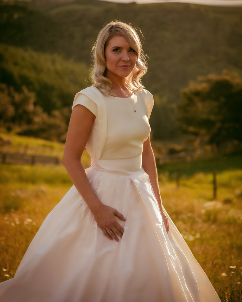 A woman in a white bridal gown stands in a field as the sun comes down