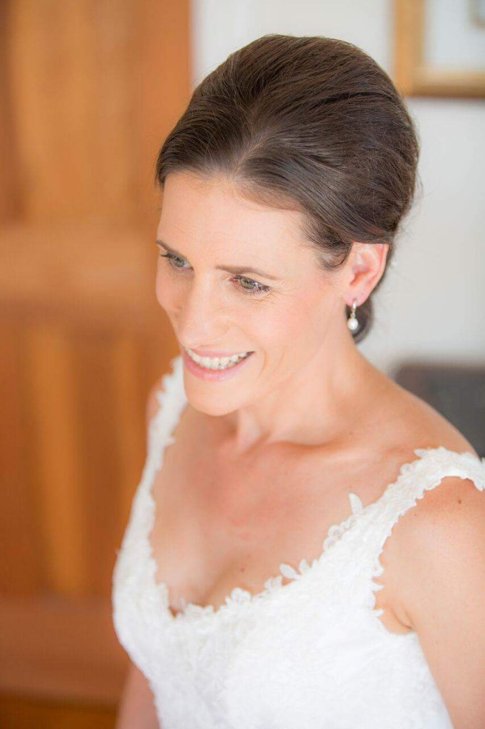 A bride in her wedding dress smiles as she prepares for her wedding