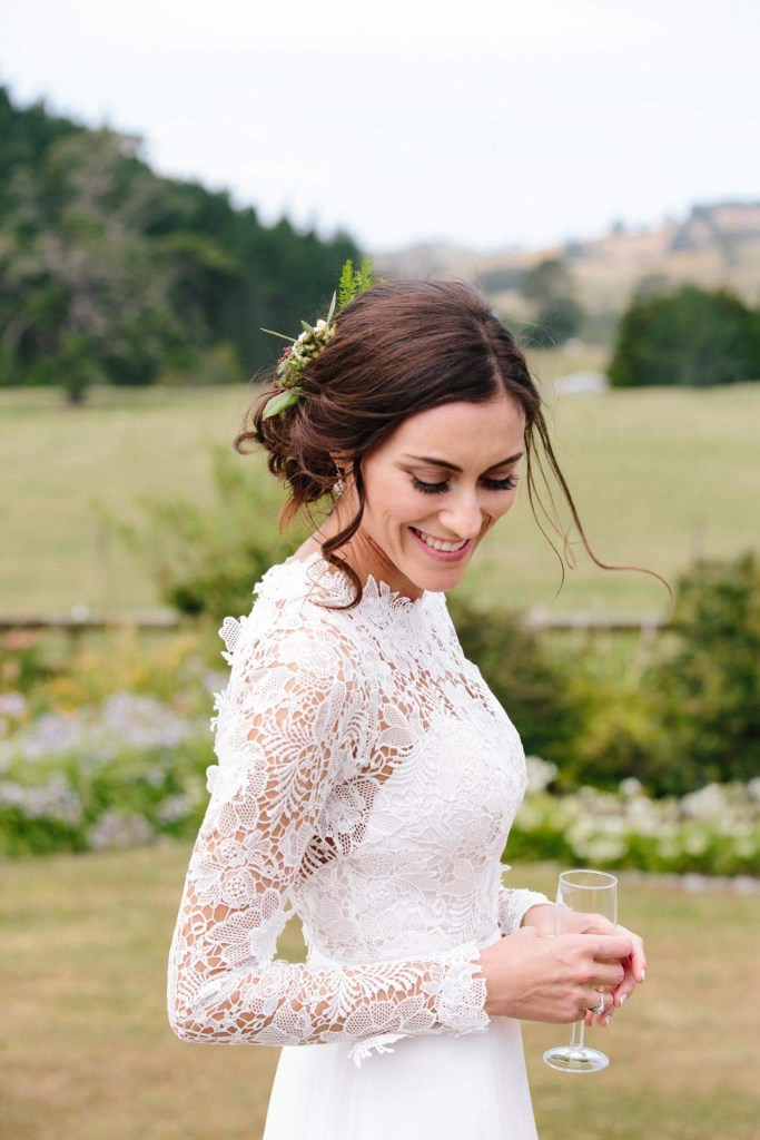 A woman smiles as she stands outside wearing a wedding dress after getting married