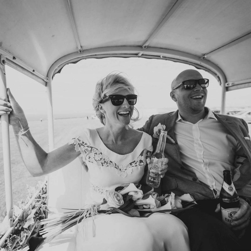 A bride in a wedding dress sits in a golf cart with her husband after their wedding