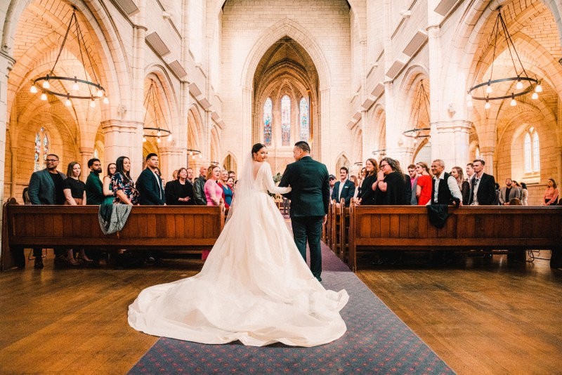 A woman walks down the church aisle wearing a white bridal gown with a long train