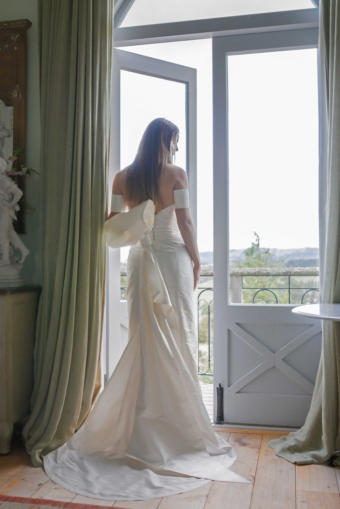 A woman in a wedding dress stands by doors with lots of glass, with countryside in the distance