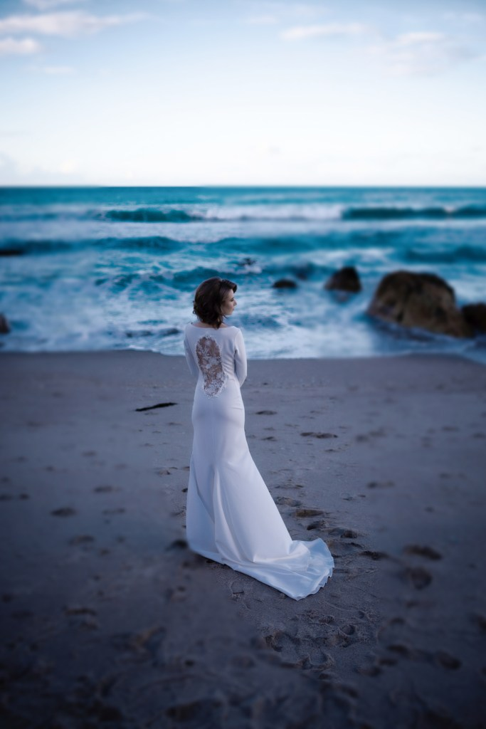 A woman stands on Mount Maunganui beach wearing one of the bridal gowns from White Silk Bridal Couture