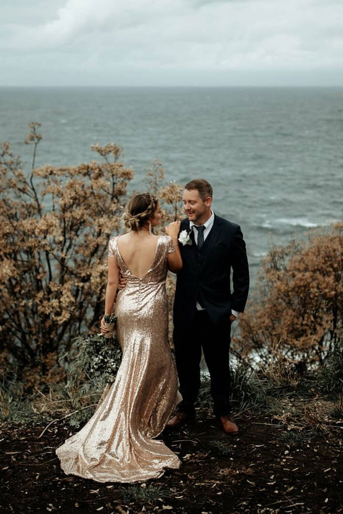 A bride and groom stand out a hill with the sea behind them
