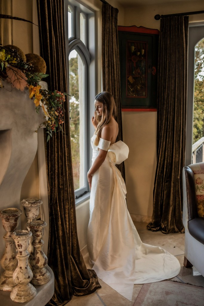 A woman stands by a window with long curtains as she wears a white bridal gown