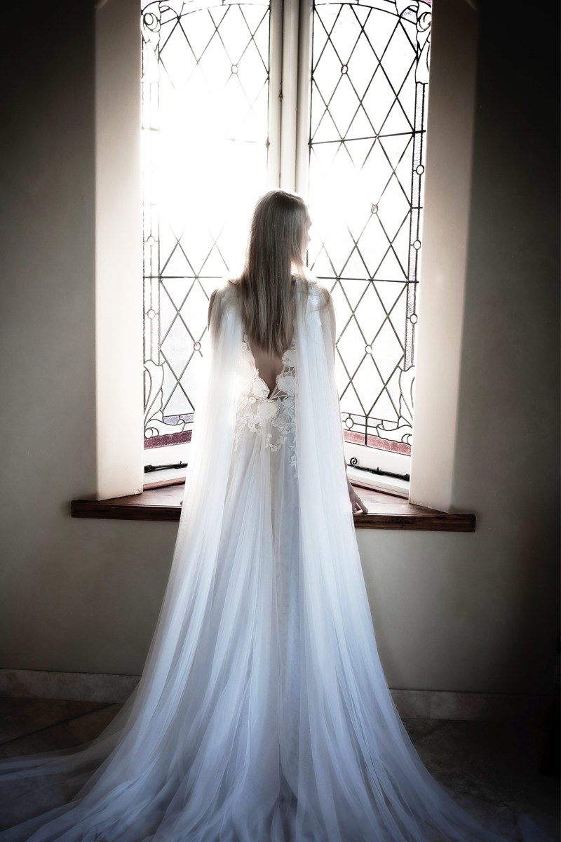 A young woman in a white bridal gown stands in front of a window with light pouring through
