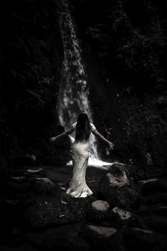 A woman in a white wedding dress stands on a rock with a waterfall in the background, as she stands with her arms out
