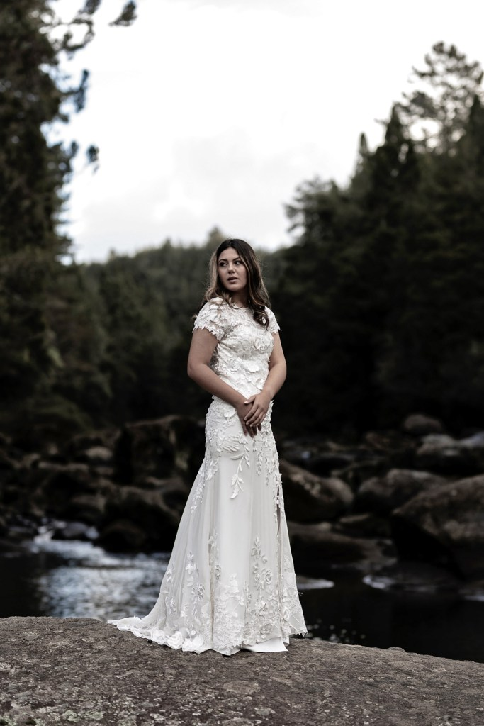 A woman in a white bridal gown stands on a rock with water behind her