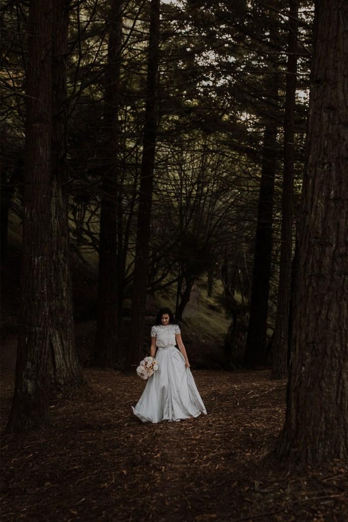 A woman with dark hair, wearing a wedding dress, walks through a forest